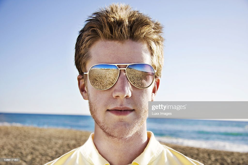 5bdc5aac9339 Portrait Of Young Man With Sunglasses At Beach Stock Photo - Getty ...