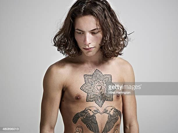 Portrait of young man with tattooed chest.