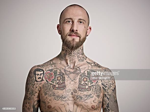 Portrait of young man with tattooed upper body.