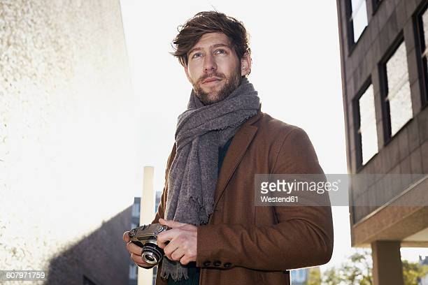 Portrait of young man with vintage camera