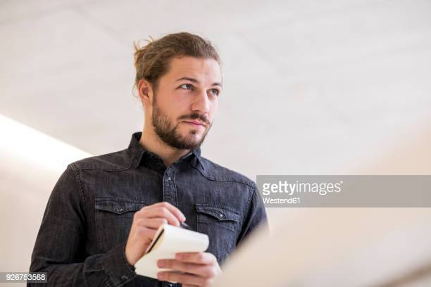 portrait of young man with wrting pad and pencil - journalist stock pictures, royalty-free photos & images