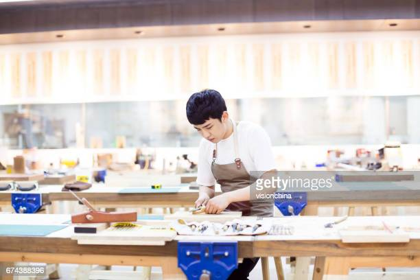 portrait of young man working in a carving workshop