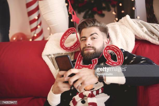 Portrait of young man wrapped in christmas decorations at christmas party