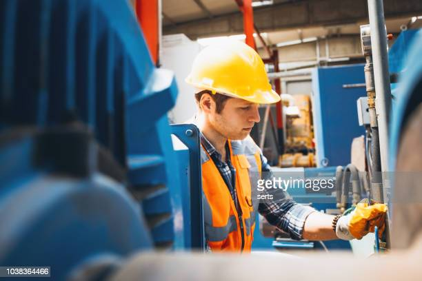 portrait of young manuel worker man working with ball valves in factory - power station stock pictures, royalty-free photos & images