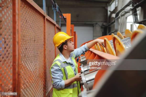 portrait of young manuel worker man working with ball valves in factory - district heating plant stock pictures, royalty-free photos & images