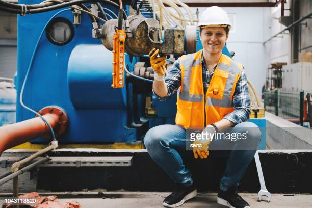 portrait of young mechanical engineer man working in factory building. - mechanical engineering stock pictures, royalty-free photos & images
