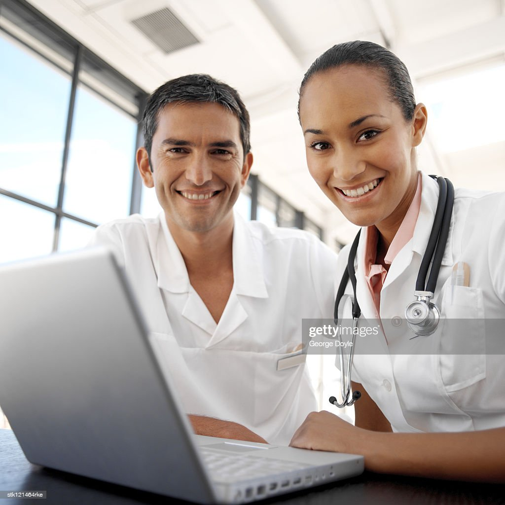 portrait of young medical personnel in front of a laptop : Photo