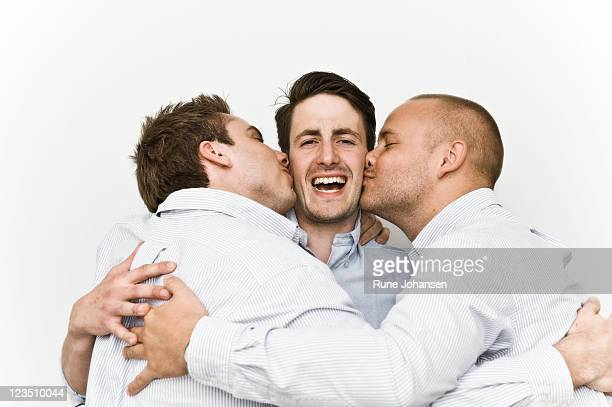Portrait of young men kissing their fellow member of Secret society on the cheek, Denmark