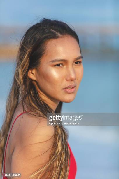 Portrait of young Millennial filipino woman with long brown wavy hair enjoying Seal Beach in California standing on the sand at the edge of the ocean near the waves and water holding a surfboard
