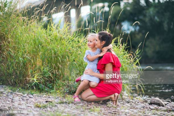 A portrait of young mother and a toddler daughter by the river outdoors in nature in summer.