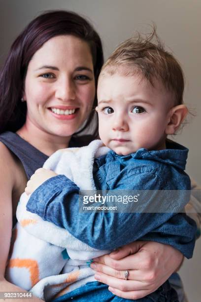 Portrait of young mother and baby son at home.