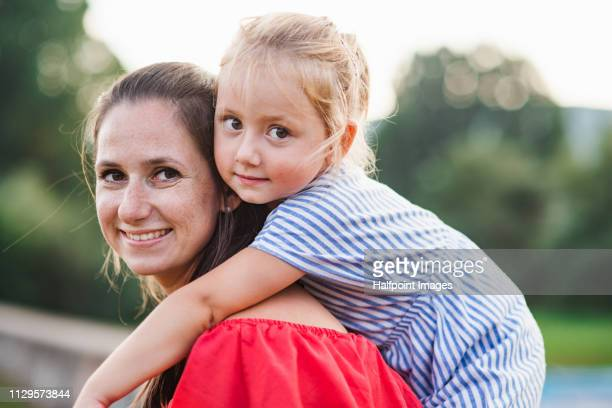 A portrait of young mother giving a piggyback ride to a toddler daughter outdoors in nature in summer.