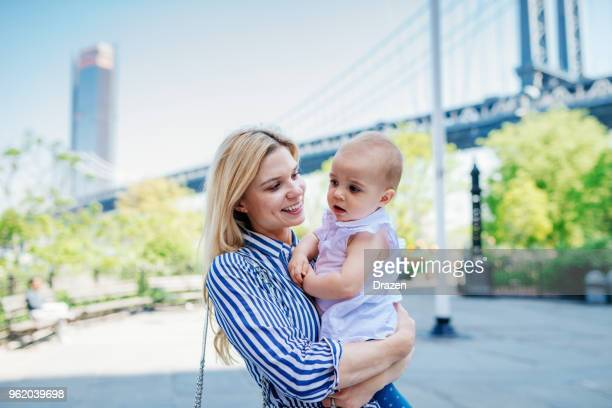 Portrait of young mother with baby near Manhattan Bridge