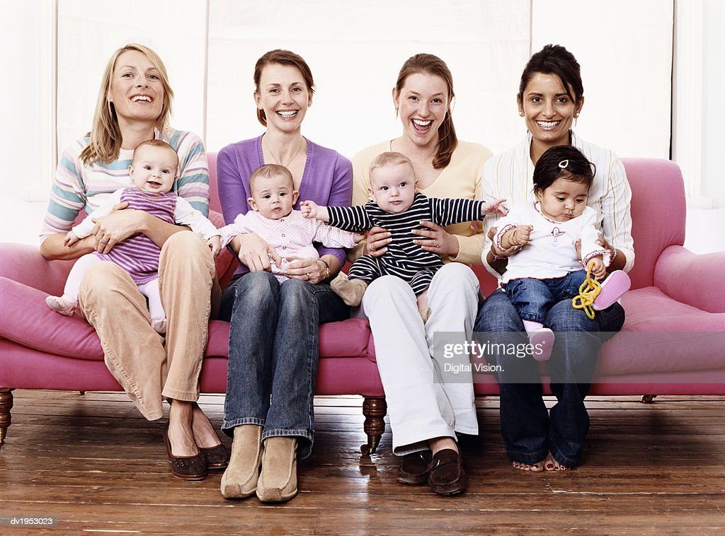 Portrait of Young Mothers with Their Children on a Sofa : Stock Photo