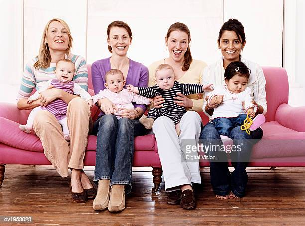 portrait of young mothers with their children on a sofa - middelgrote groep mensen stockfoto's en -beelden