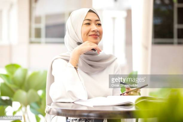 portrait of young muslim college girl at a cafe - malaysia beautiful girl stock photos and pictures