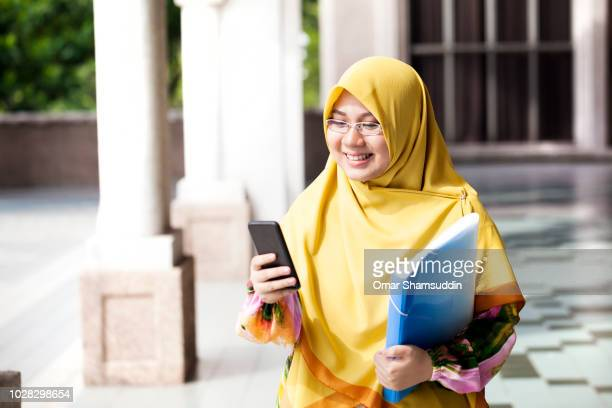 Portrait of young Muslim girl in hijab with smartphone