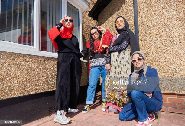 portrait of young muslim women in backyard - female friendship stock pictures, royalty-free photos & images