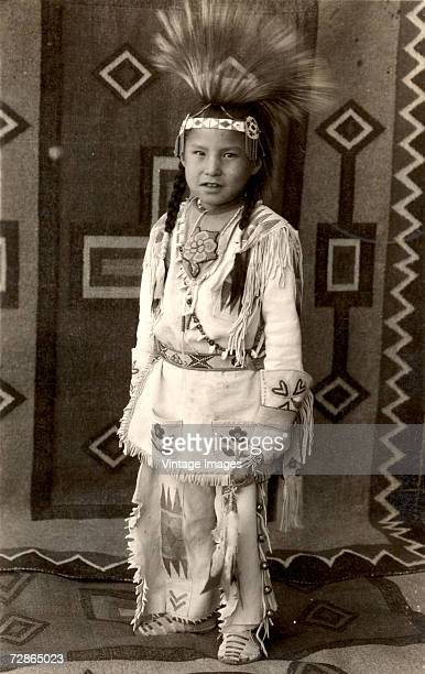 Portrait of young Native American Calvin Last Star as he poses in traditional clothing complete with a tall headdress Browning Montana late 1930s