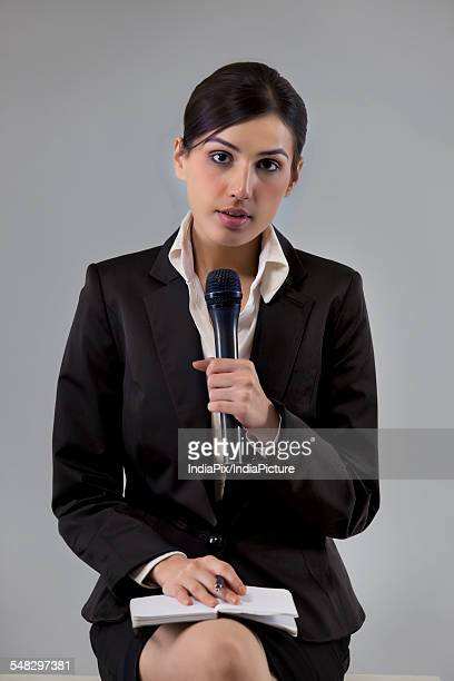 Portrait of young news reporter holding microphone with notepad