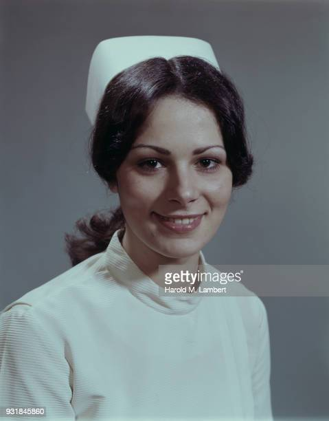 Portrait of young nurse in uniform, smiling, close-up