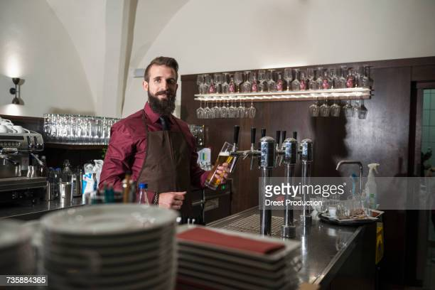 Portrait of young owner filling glass of beer at restaurant