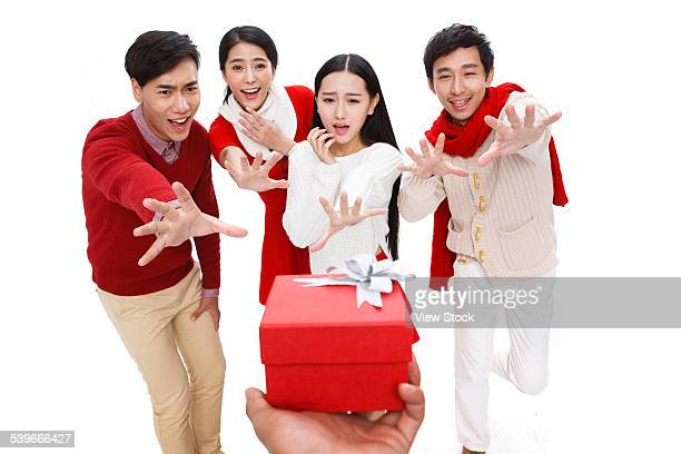 Portrait of young people reaching for gift box
