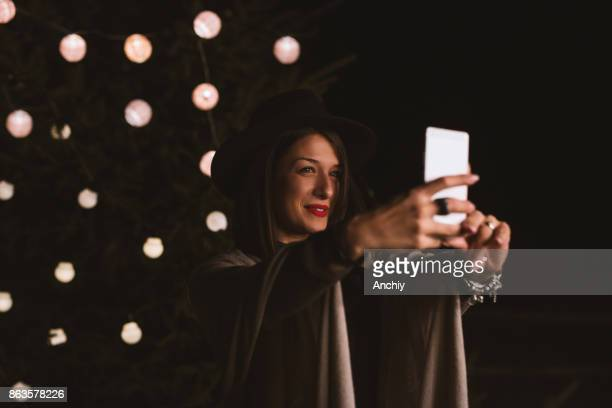 Portrait of young pretty woman taking selfie in front of decorated tree.