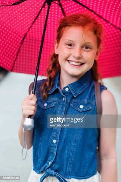 """portrait von junge rothaarige mädchen unter roten regenschirm am morgen schule. - """"martine doucet"""" or martinedoucet stock-fotos und bilder"""