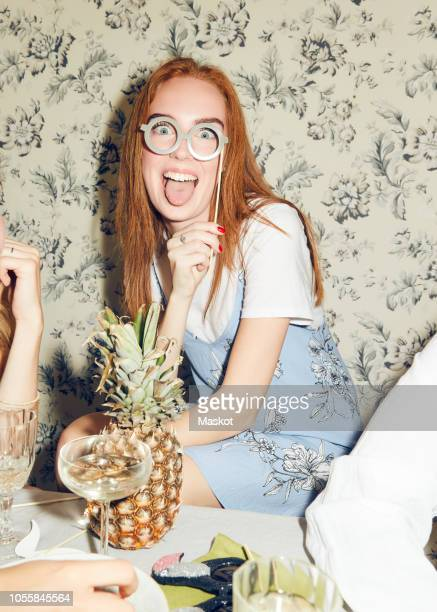 portrait of young redhead woman holding prop while sitting amidst friends during dinner party at home - 小道具 ストックフォトと画像