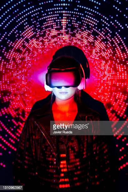 portrait of young self-confident woman in vr glasses. she is in front of the projection screen, lighted with colorful neon code - google stock pictures, royalty-free photos & images
