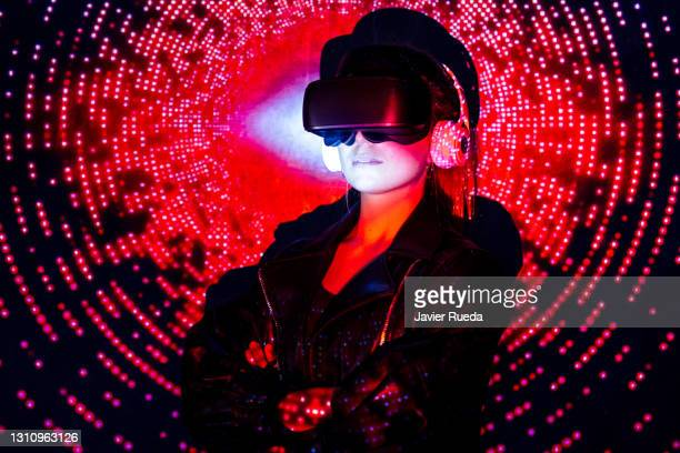 portrait of young self-confident woman in vr glasses. she is standing against projection screen, lighted with colorful neon code - google stock pictures, royalty-free photos & images