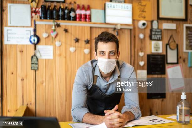 portrait of young small business man owner with face mask at checkout - protection stock pictures, royalty-free photos & images