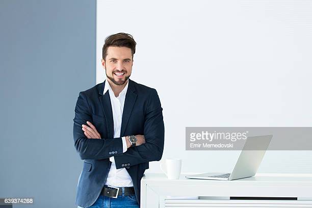 Portrait of young smiling businessman with arms crossed.