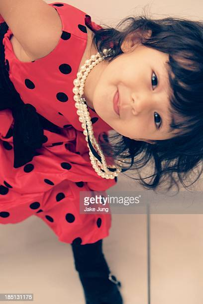 Portrait of young smiling girl in pink dress