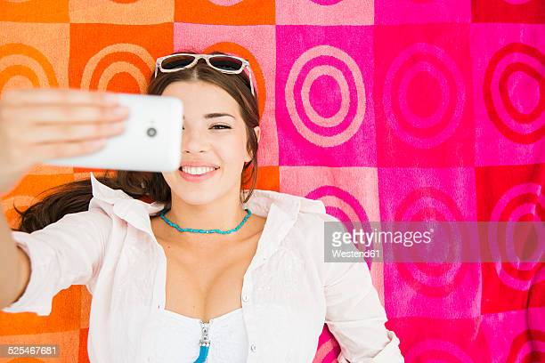 Portrait of young smiling woman lying on beach towel taking a selfie, elevated view