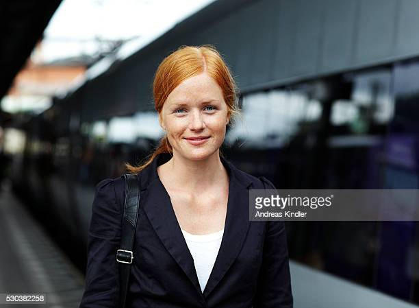 portrait of young smiling woman standing at train station - bahnhof stock-fotos und bilder