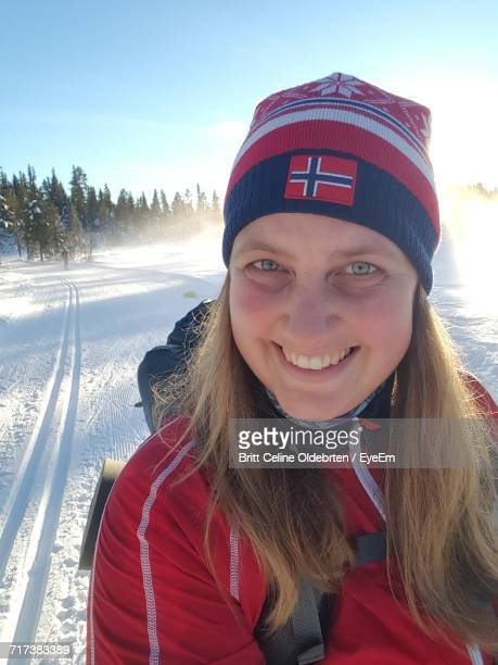portrait of young smiling woman wearing knit hat while skiing on snowy field - norwegian flag stock pictures, royalty-free photos & images