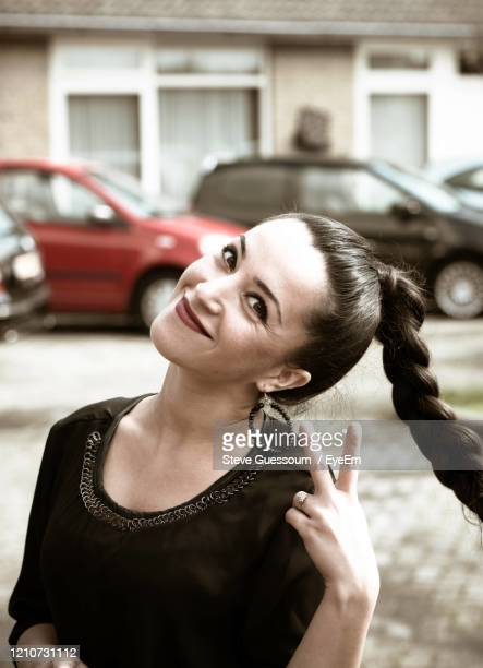 portrait of young smiling woman with braided hair standing outdoors - 首をかしげる ストックフォトと画像
