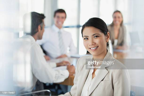 Portrait of young smiling woman with coworkers in the background