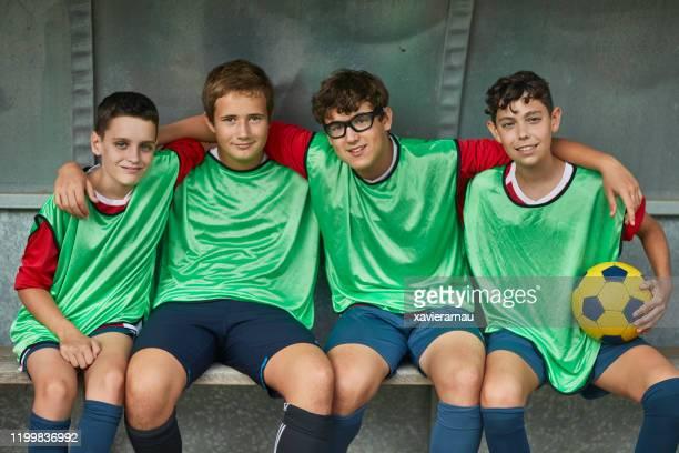 portrait of young spanish male footballers on sideline bench - desporto de equipa imagens e fotografias de stock