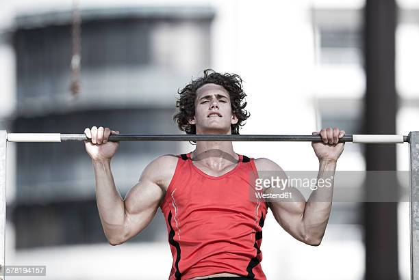 Portrait of young sportsman doing chin-ups