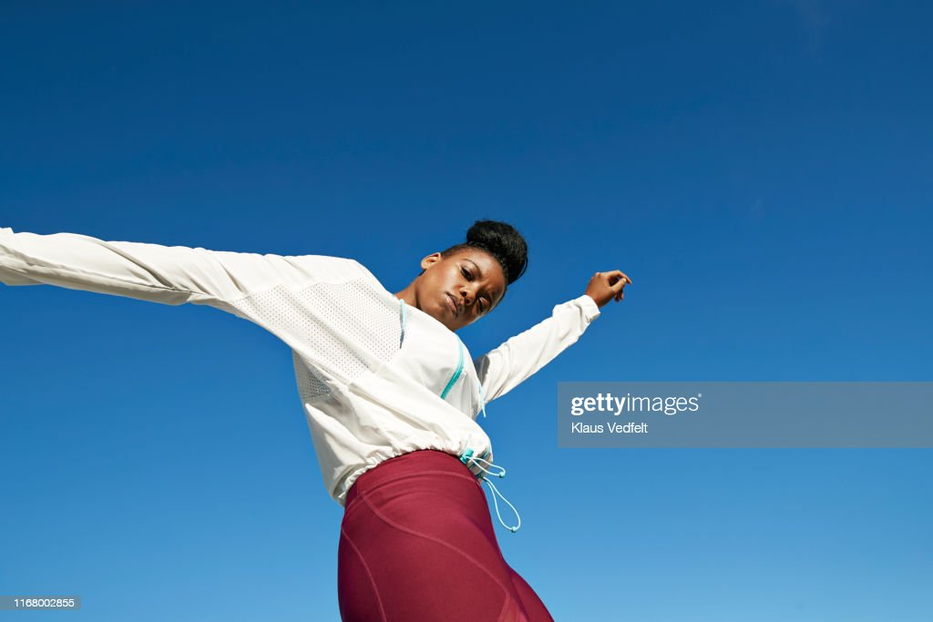 Portrait of young sportswoman against clear blue sky : Stock-Foto