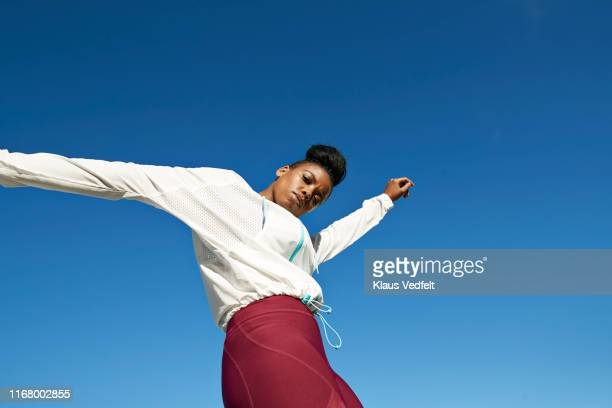 portrait of young sportswoman against clear blue sky - moda fotografías e imágenes de stock