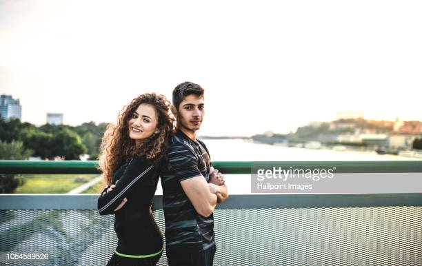 A portrait of young sporty couple standing back to back on a bridge outdoors in the city. Copy space.