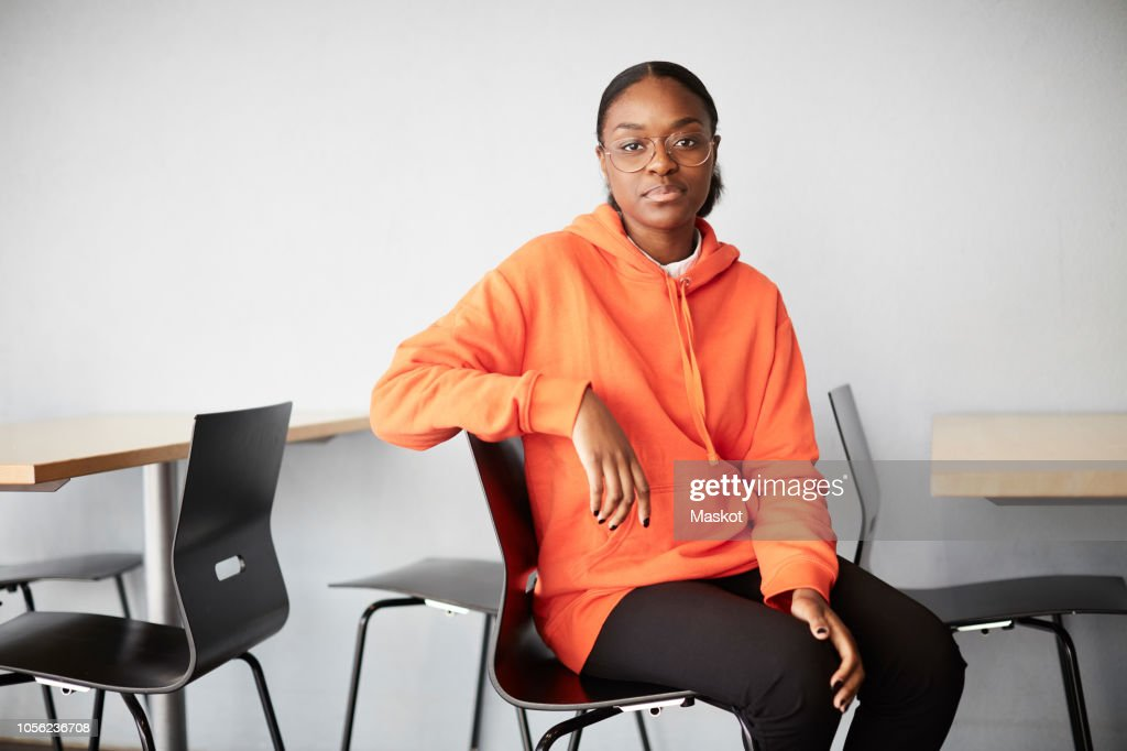 Portrait of young student sitting on chair against wall at university : Stock Photo