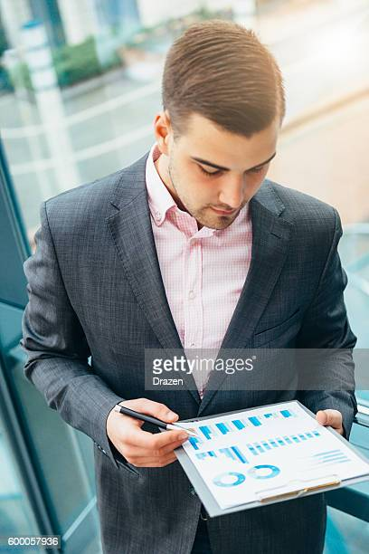 Portrait of young successful businessman holding financial reports
