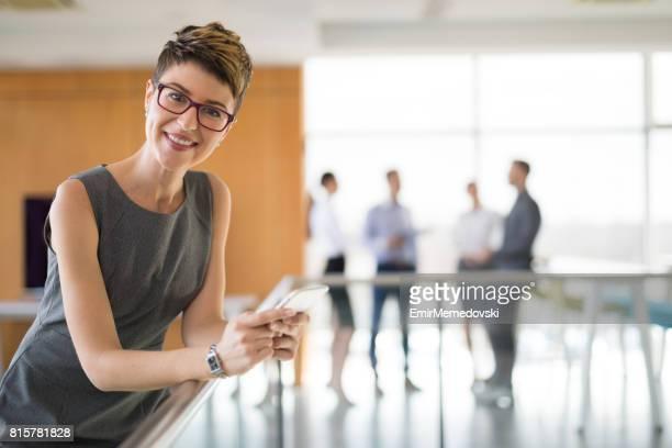 Porträt des jungen erfolgreichen Geschäftsfrau halten Handys
