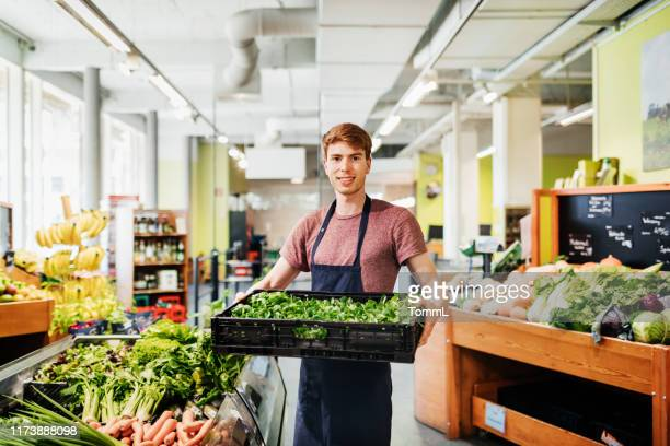 portrait of young supermarket clerk holding crate of vegetables - produce aisle stock pictures, royalty-free photos & images