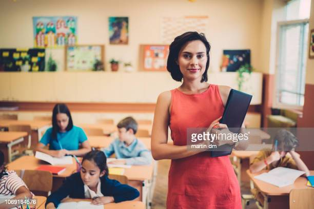 Portrait of young teacher in class teaching the students